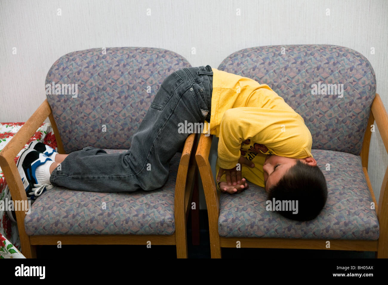 7-8 years old Hispanic  adhd boy waiting for his appointment with the doctor. MR  © Myrleen Pearson - Stock Image
