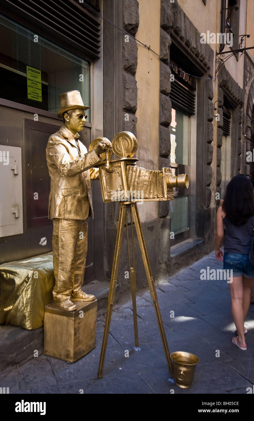 Gold Photographer Mime Artist Statue seen in Sienna Tuscany Italy - Stock Image