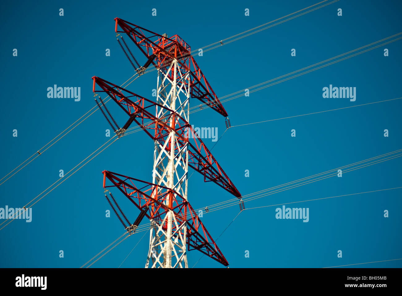 Energy transmission towers against a blue sky - Stock Image