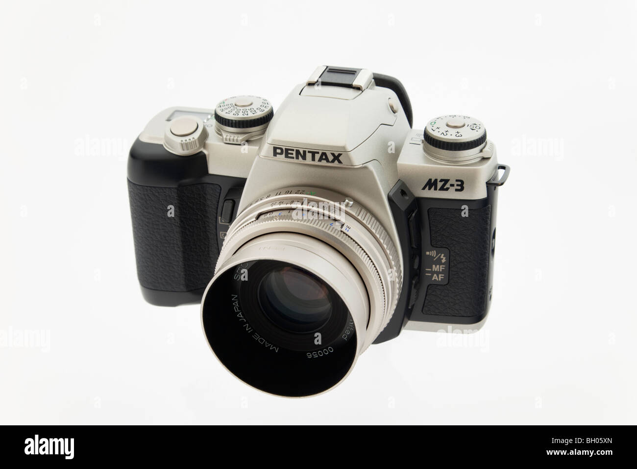 Studio still life. Pentax MZ3 retro style black and silver 35mm SLR film camera and lens on white background - Stock Image
