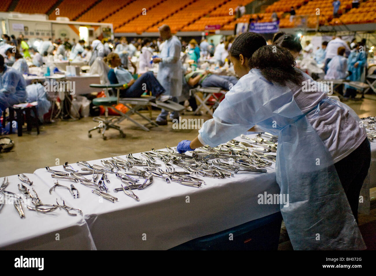 Sterilized dental instruments are laid out on a long table while hundreds of indigent people receive free dental - Stock Image