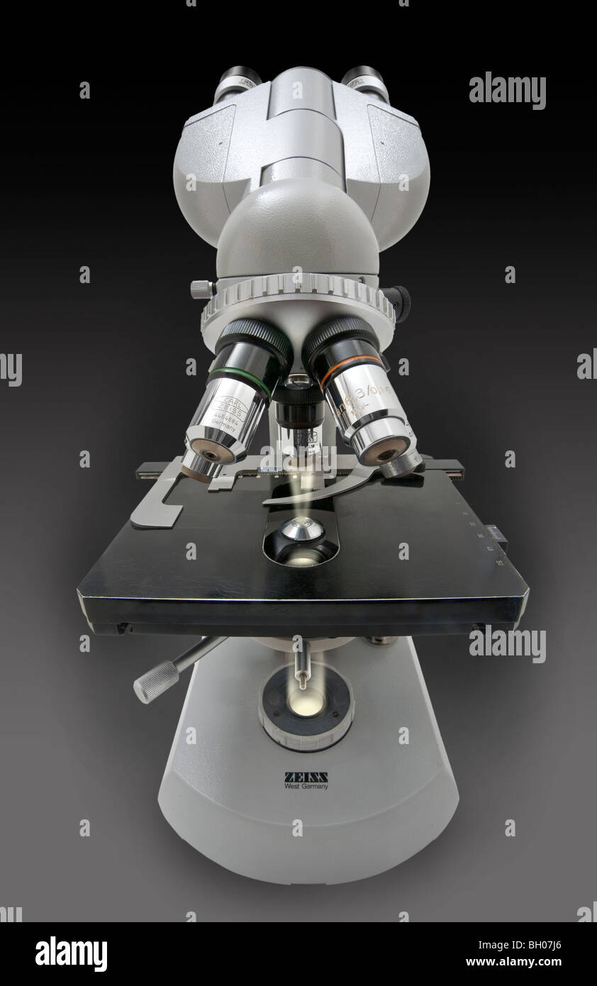 Front distorted view of a Zeiss standard compound microscope with the light path displayed from field iris to objective - Stock Image