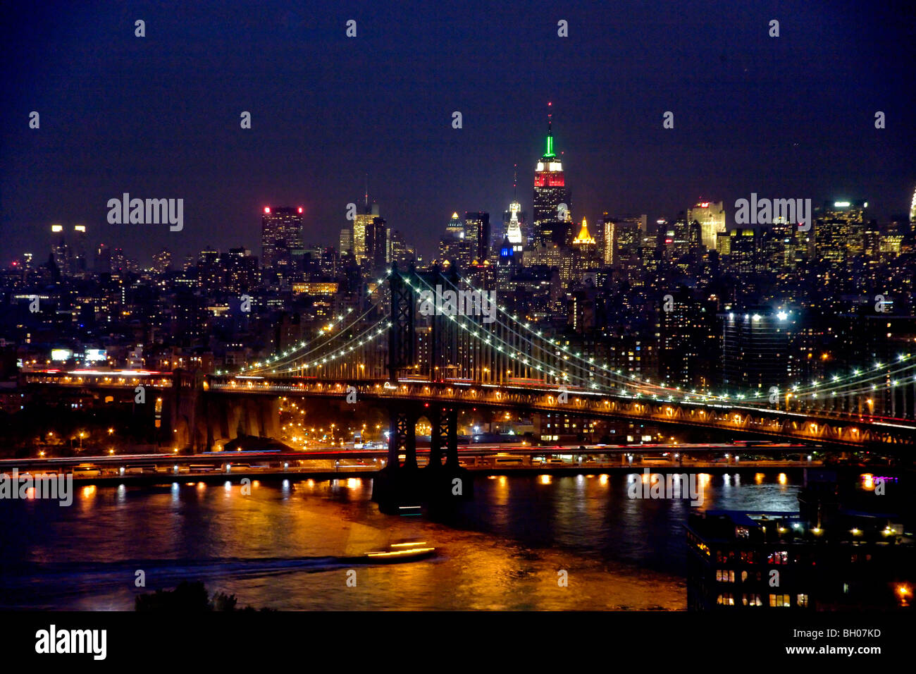 The lights of midtown Manhattan, NY City, sparkle at twilight beyond the Manhattan Bridge across the East River. - Stock Image