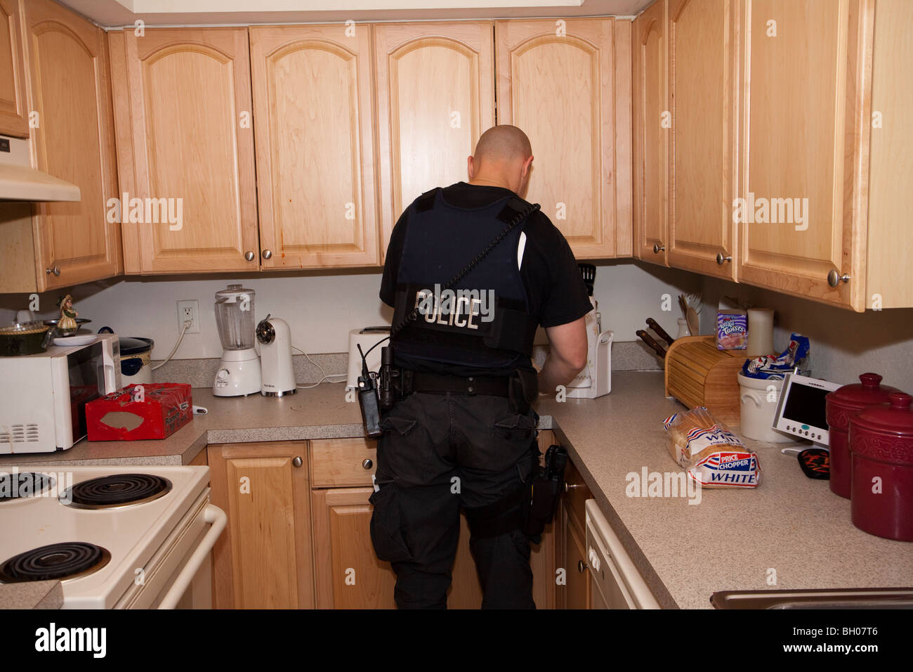 Police Officer searching kitchen. Drug related search warrant. Kansas City, MO, PD Street Narcotics Unit. - Stock Image