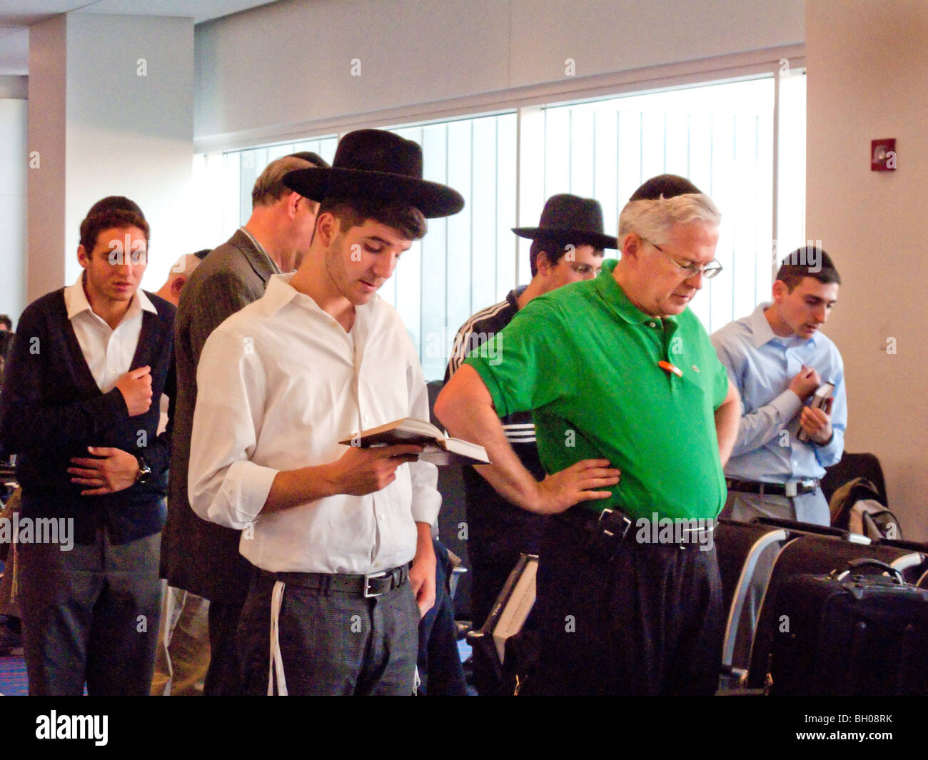 Observant orthodox Jewish men say their evening prayers while waiting to travel at New York City's John F. Kennedy - Stock Image