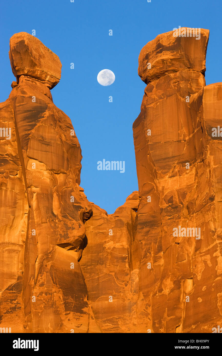 Near full moon along with the Three Gossips, Arches National Park, near Moab, Utah. - Stock Image