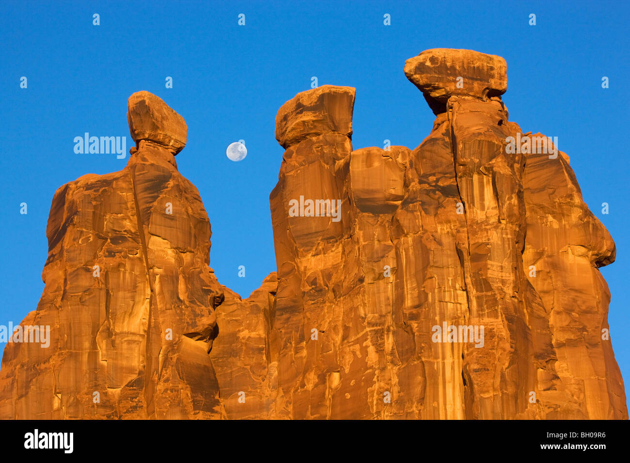 Near full moon along with the Three Gossips, Arches National Park, near Moab, Utah. Stock Photo