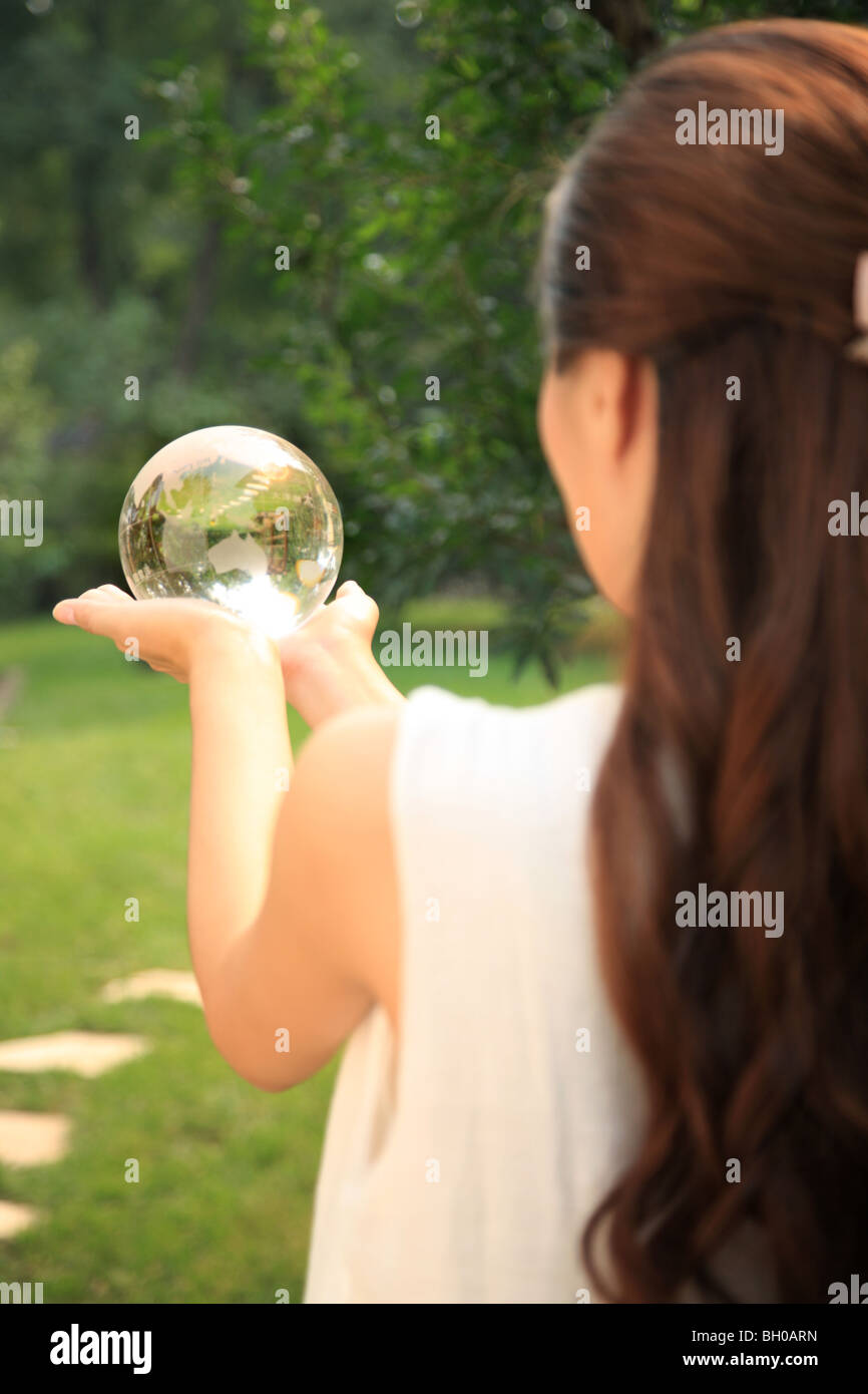 young woman holding crystal ball - Stock Image