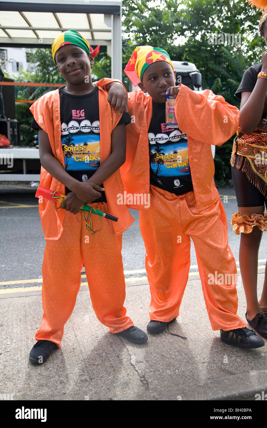Two young boys in orange suit carnival costumes. Notting Hill Carnival. Notting Hill. London. England. UK - Stock Image