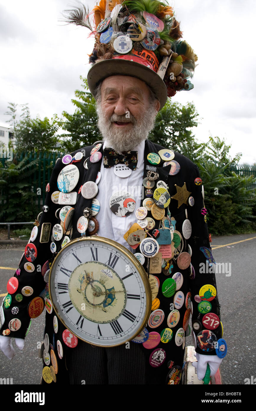 Bearded old man in carnival costume. Lots of badges & top hat. Notting Hill Carnival, Notting Hill. London. - Stock Image