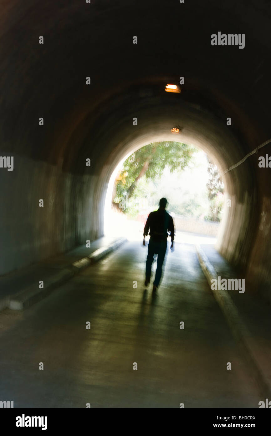 Mysterious blurred male figure walking in tunnel. - Stock Image