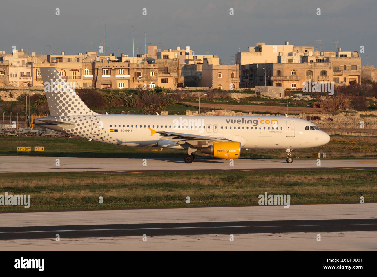 Low cost air travel and mass tourism. Vueling Airbus A320 taxiing for departure from Malta at sunset - Stock Image