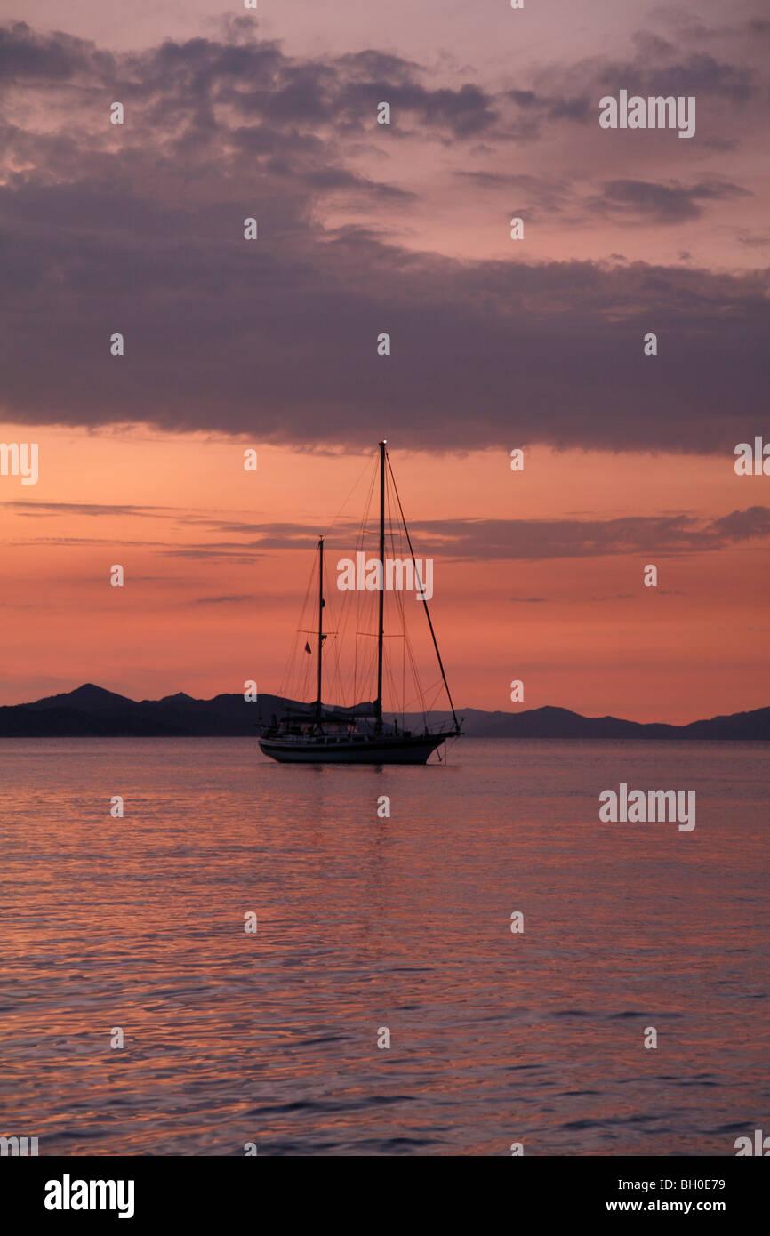 Moored yacht at  sunset Donje Celo harbour, Kolocep, South Dalmatia Croatia one of the Elaphite islands near Dubrovnik Stock Photo