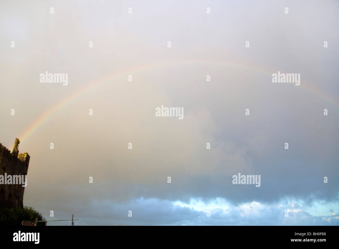 Rainbow stormy clouds Llaugharne castle Pembrokeshire Wales UK Horizontal - Stock Image