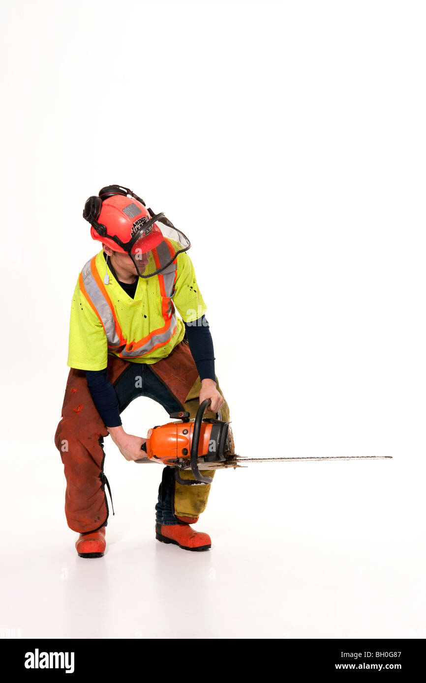 A lumberjack in full protective gear holds his chainsaw at an angle. - Stock Image