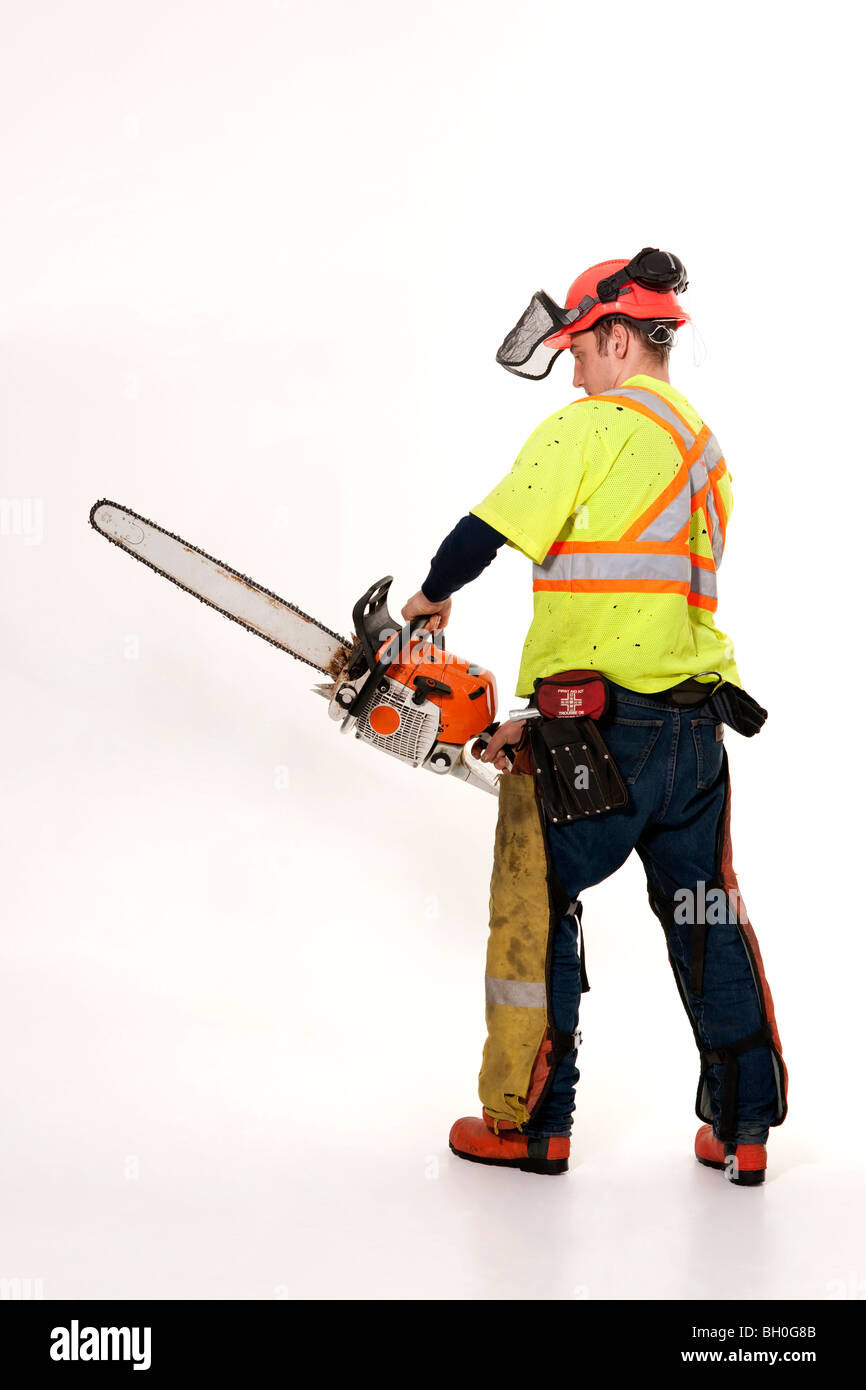 A forestry worker in protective gear holds his chainsaw. - Stock Image