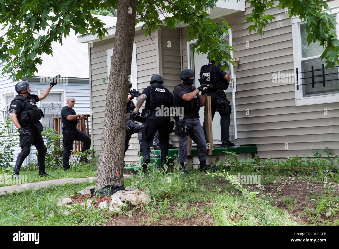 Police from tactical team making entry to serve a high-risk drug related search warrant. Street Narcotics Unit. - Stock Image