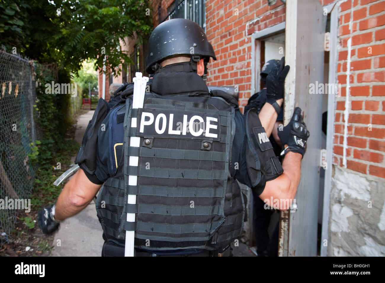 Police tactical team getting ready to enter apartment building to serve a high-risk drug related search warrant. - Stock Image