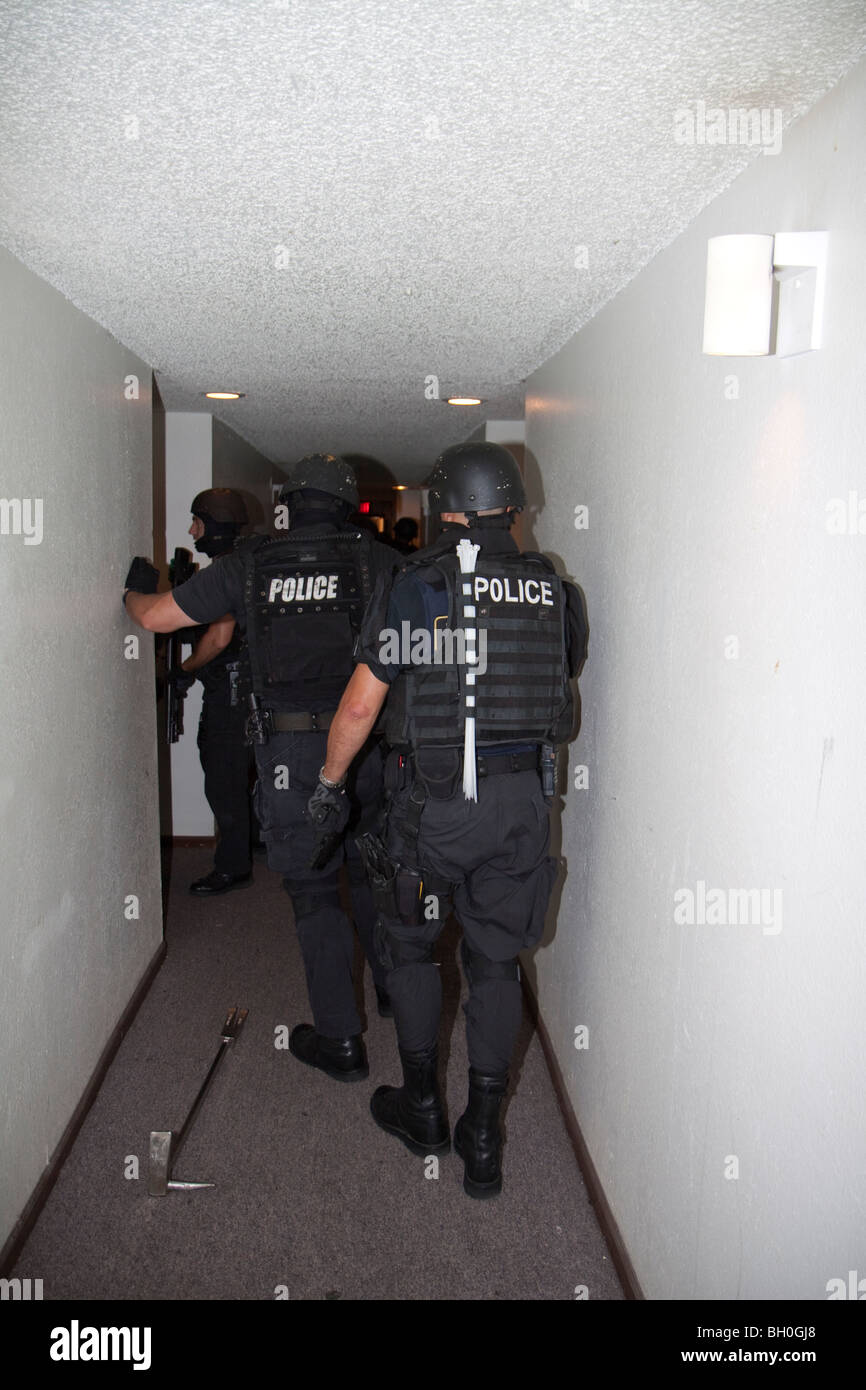 Tactical squad from Street Narcotics Unit in Kansas City, MO, entering apartment and serve a narcotics related search - Stock Image