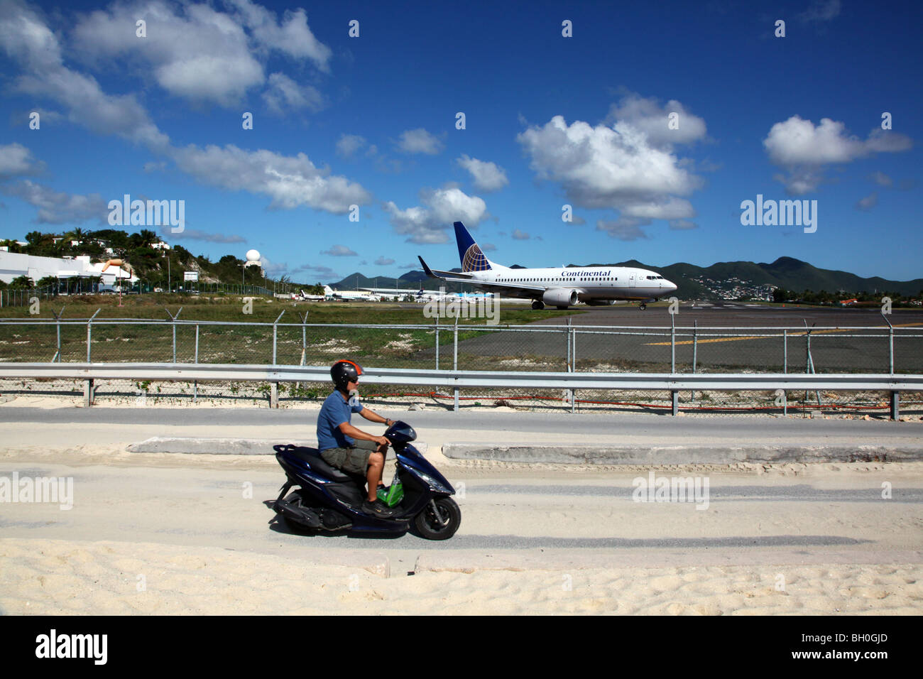 Man riding scooter near Continental Airlines 737 on tarmac - Stock Image