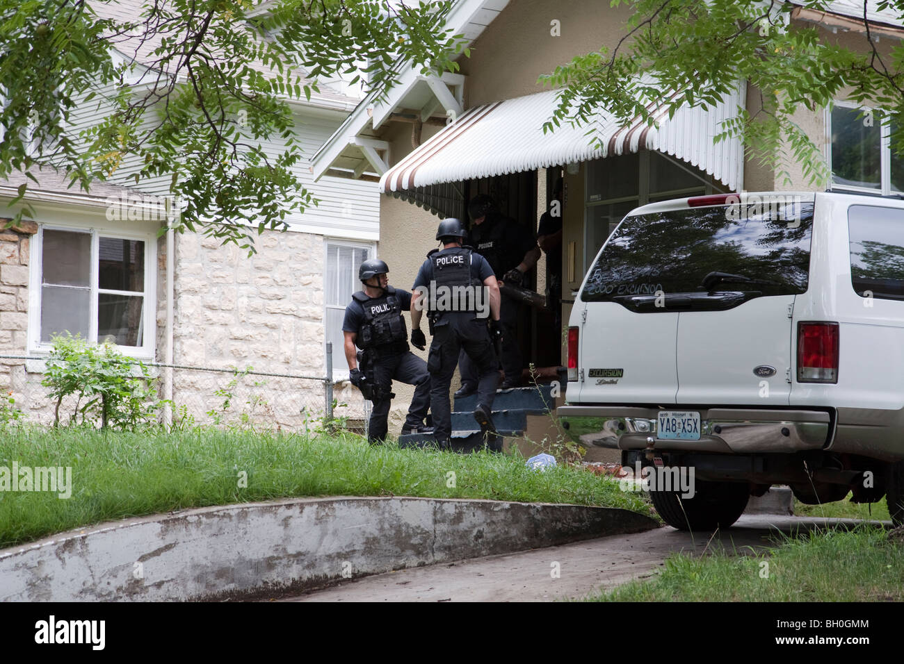 Police officers making entry to serve high-risk drug related search warrant. Street Narcotics Unit tactical squad, - Stock Image
