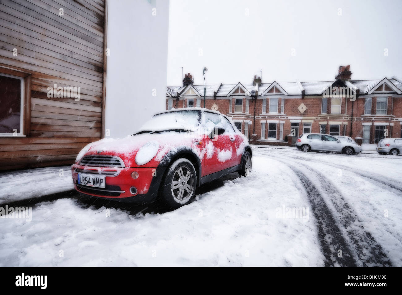 Snowing in Sussex - image of a residential street covered by snow with red Mini Cooper in the foreground - Gaussian - Stock Image