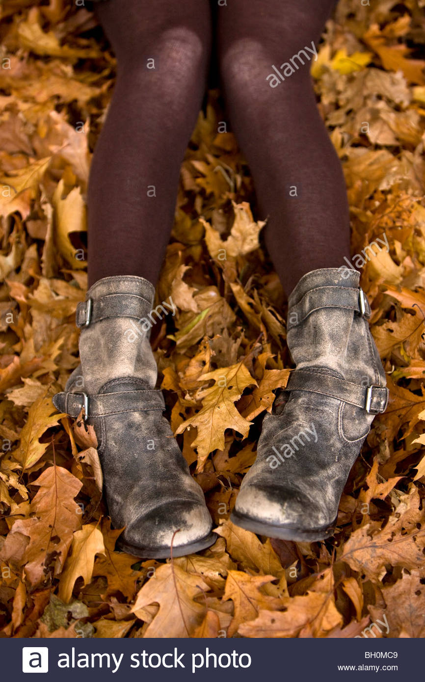 Woman's legs and feet in autumn leaves - Stock Image