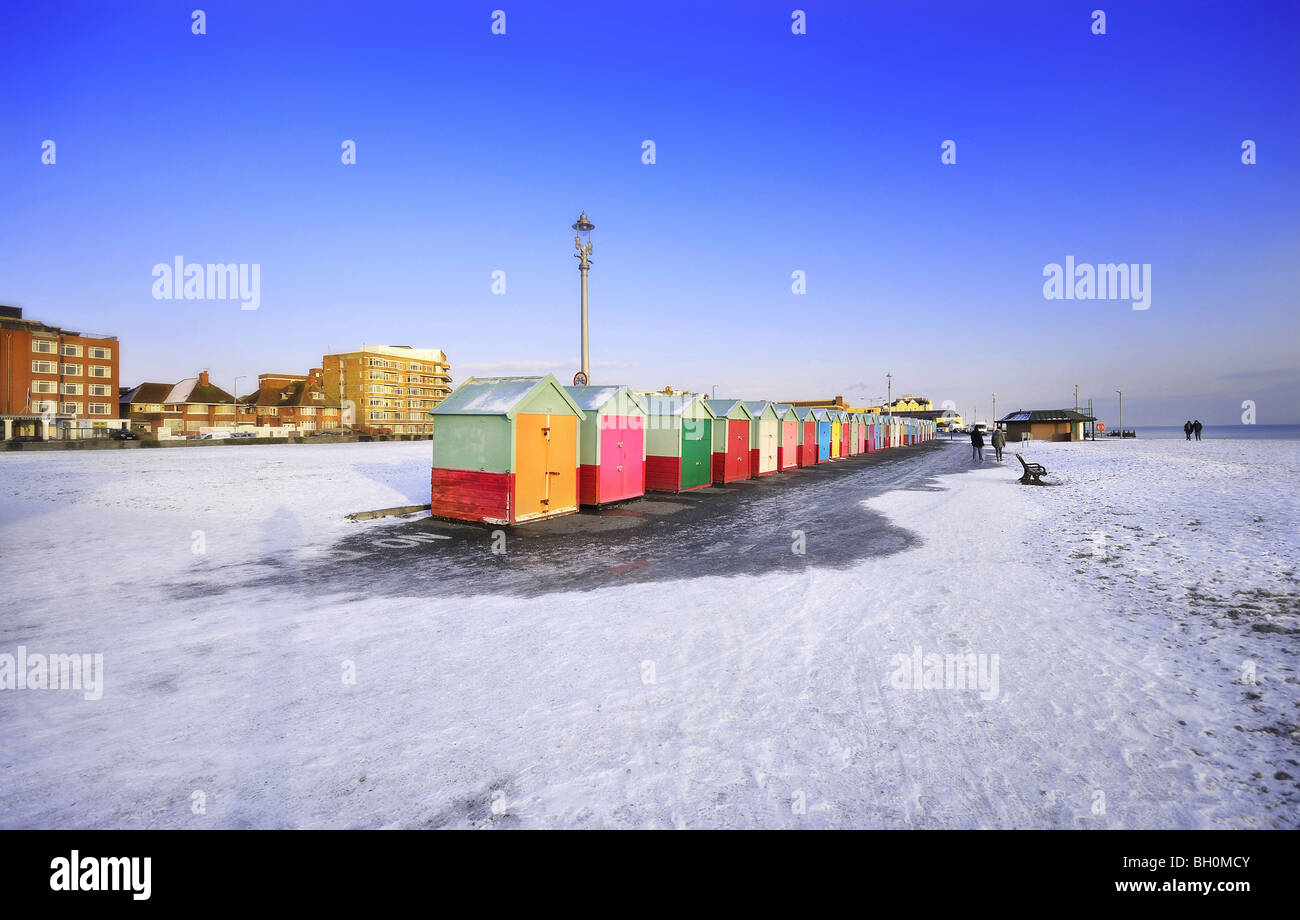 Snow on Brighton and Hove Beach with the colourful beach huts in the foreground Stock Photo