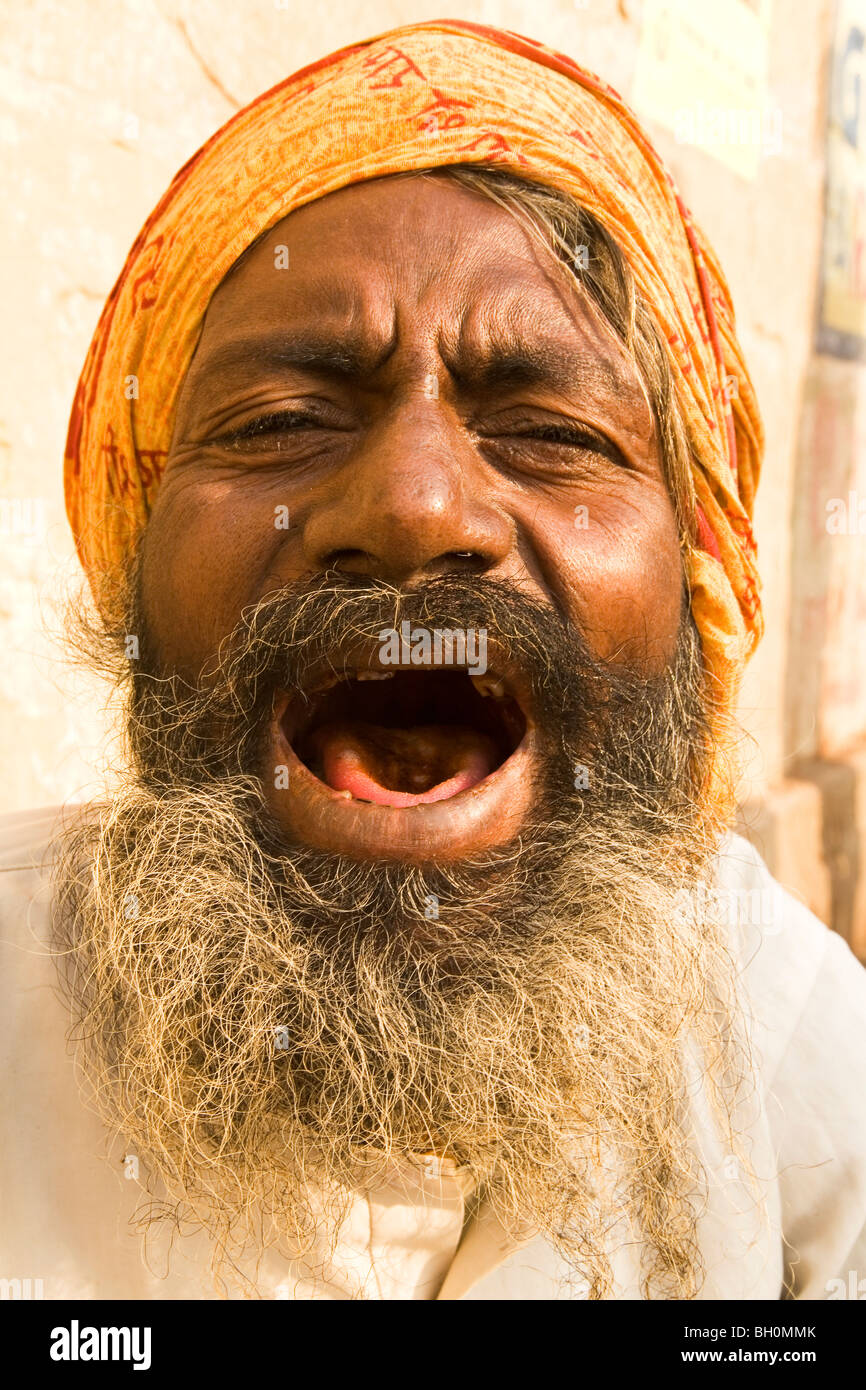 A bearded Indian man shows off his teeth in the ancient city of Varanasi, India - Stock Image