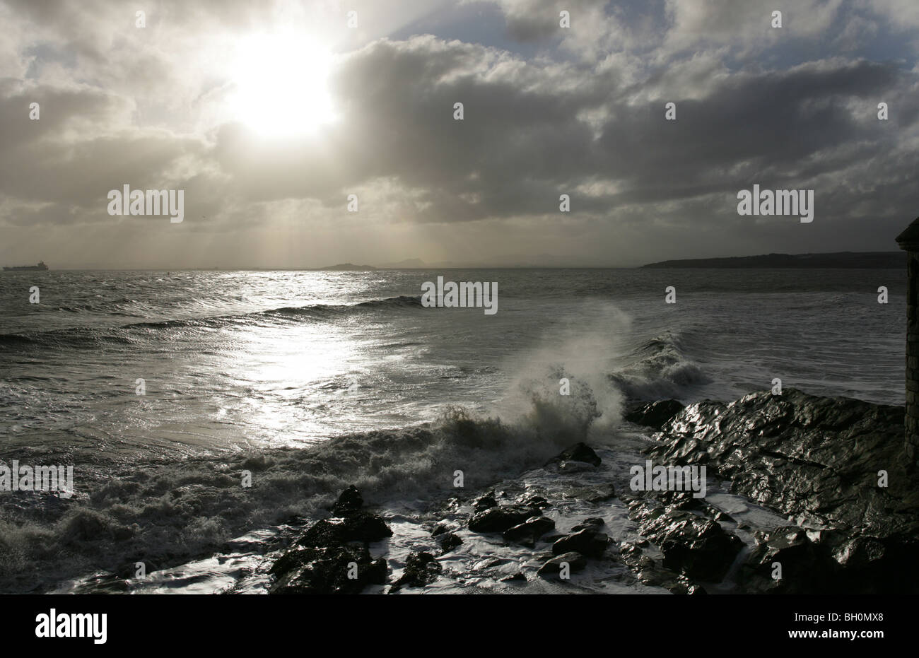 Dramatic skies and waves breaking on rocks at Ravenscraig Park near kirkcaldy Fife - Stock Image