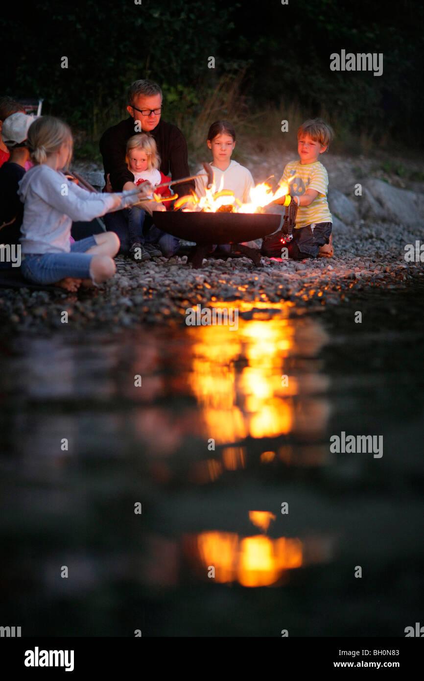 Children and man grilling at Lake Starnberg, Bavaria, Germany - Stock Image