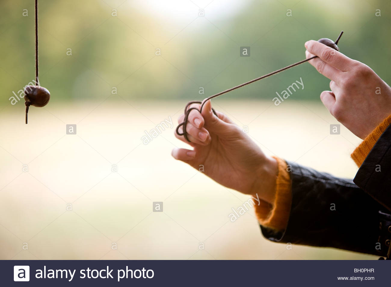A young woman playing conkers - Stock Image