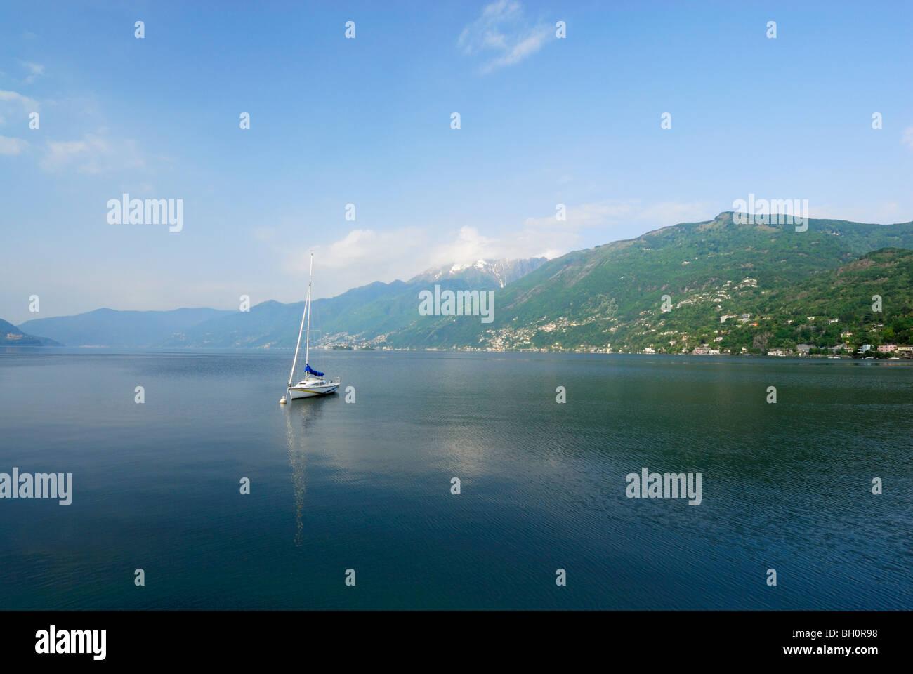 Sailing boat anchored at lake Maggiore with Gridone and Pizzo Leone in the background, Ascona, lake Maggiore, Lago - Stock Image