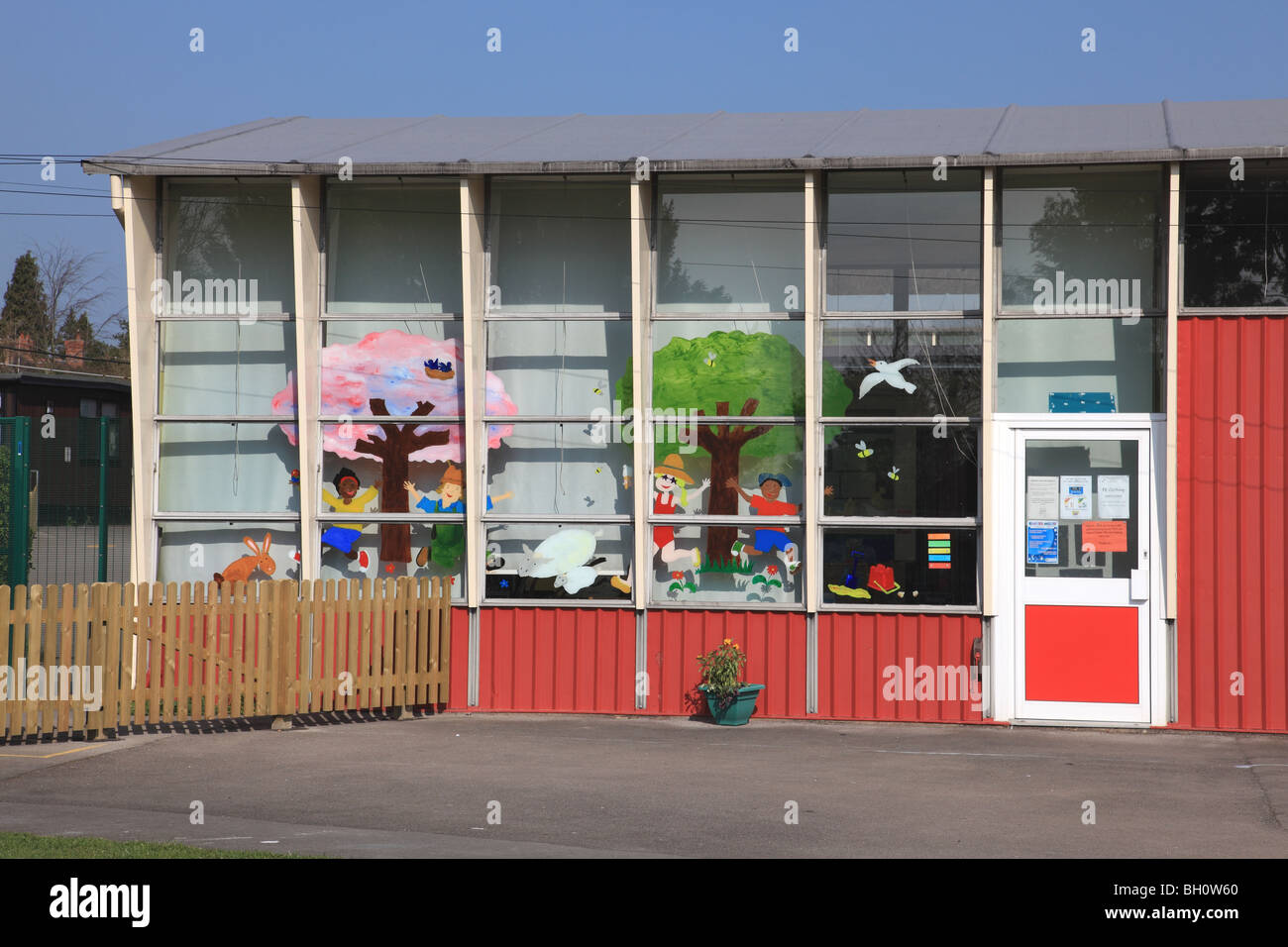 Exterior of an infants' school classroom with bright colourful paintings of trees, children and animals - Stock Image