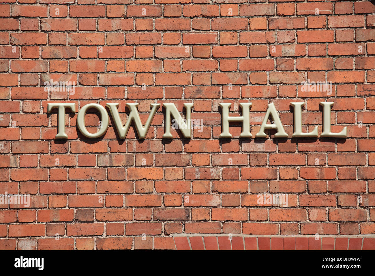 Town Hall sign in gold capital letters on a brick wall - Stock Image