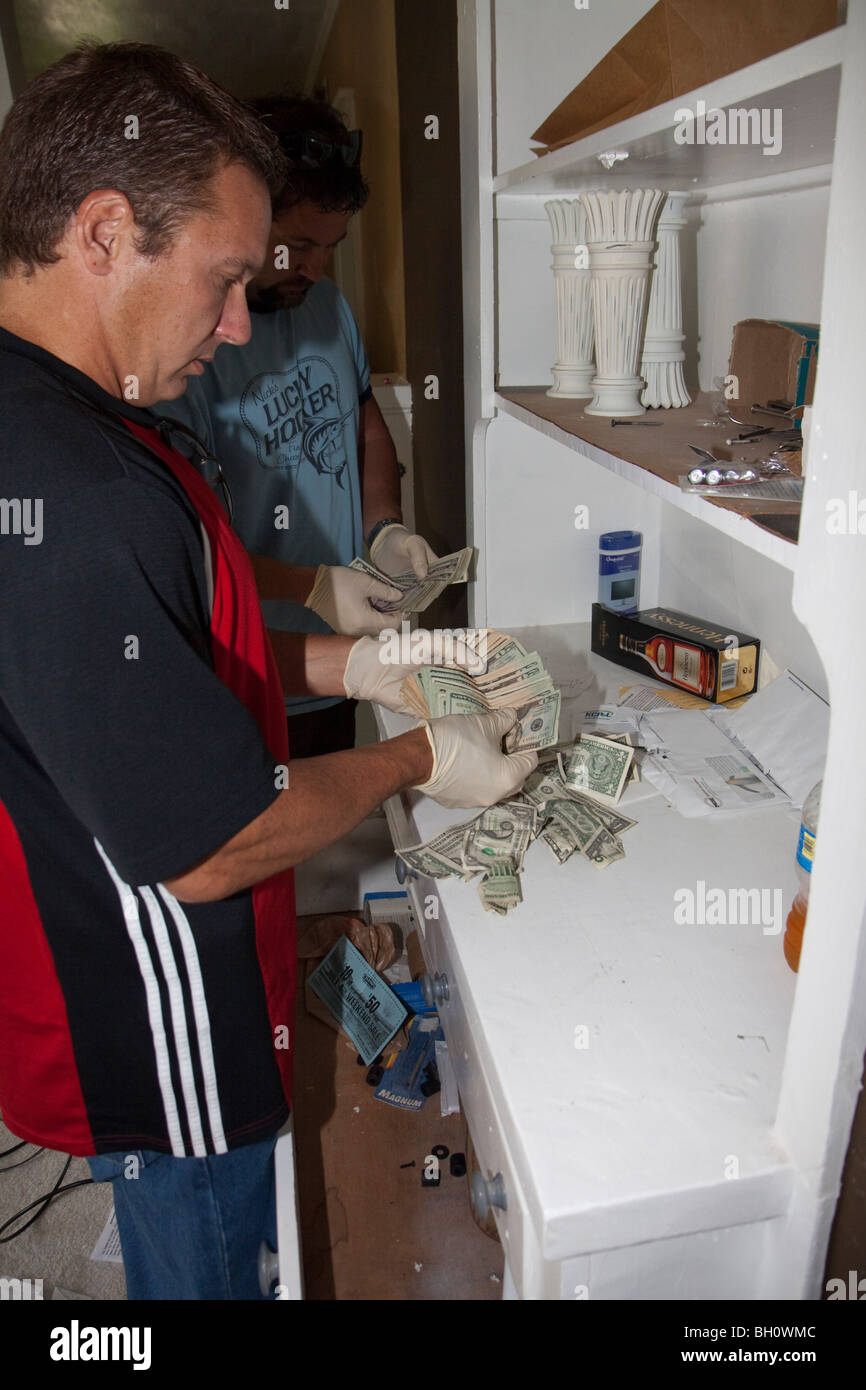 Police officers from the Gang Squad is counting currency found at a narcotics related search warrant. Kansas City, - Stock Image