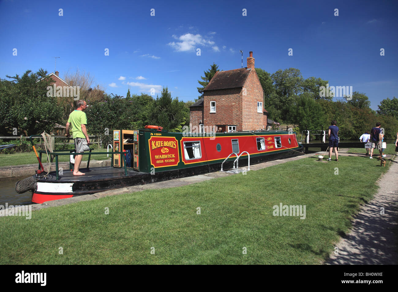 Holiday cruising on the Grand Union Canal in the lock by the Crooked House cottage at Braunston, Northamptonshire - Stock Image