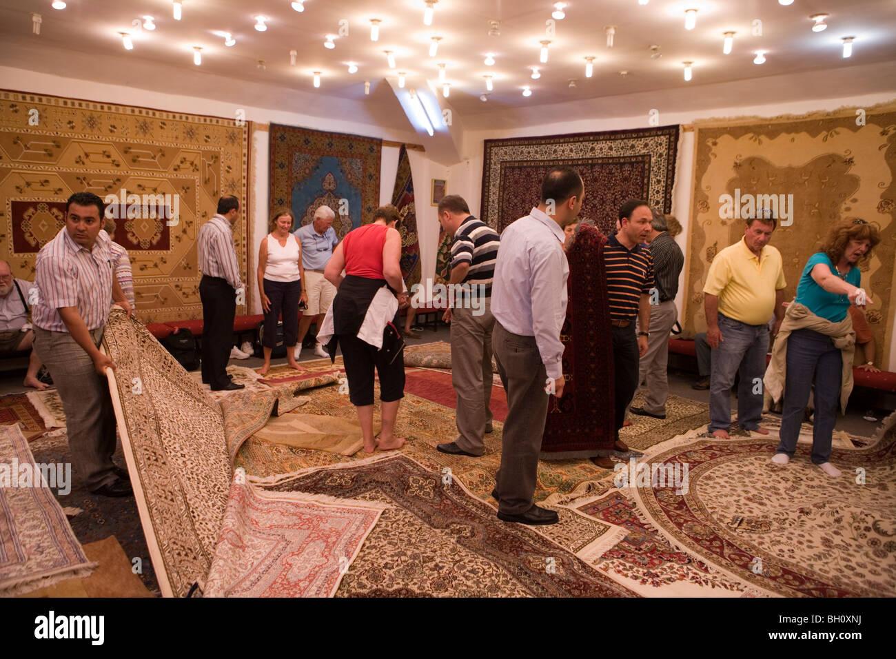 People looking at carpets at a Rug Factory, Dalyan, Turkey, Europe - Stock Image
