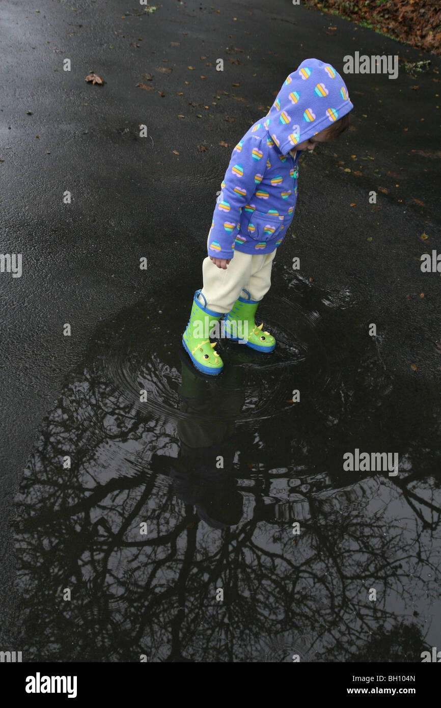 A young child walking in a rain puddle. - Stock Image