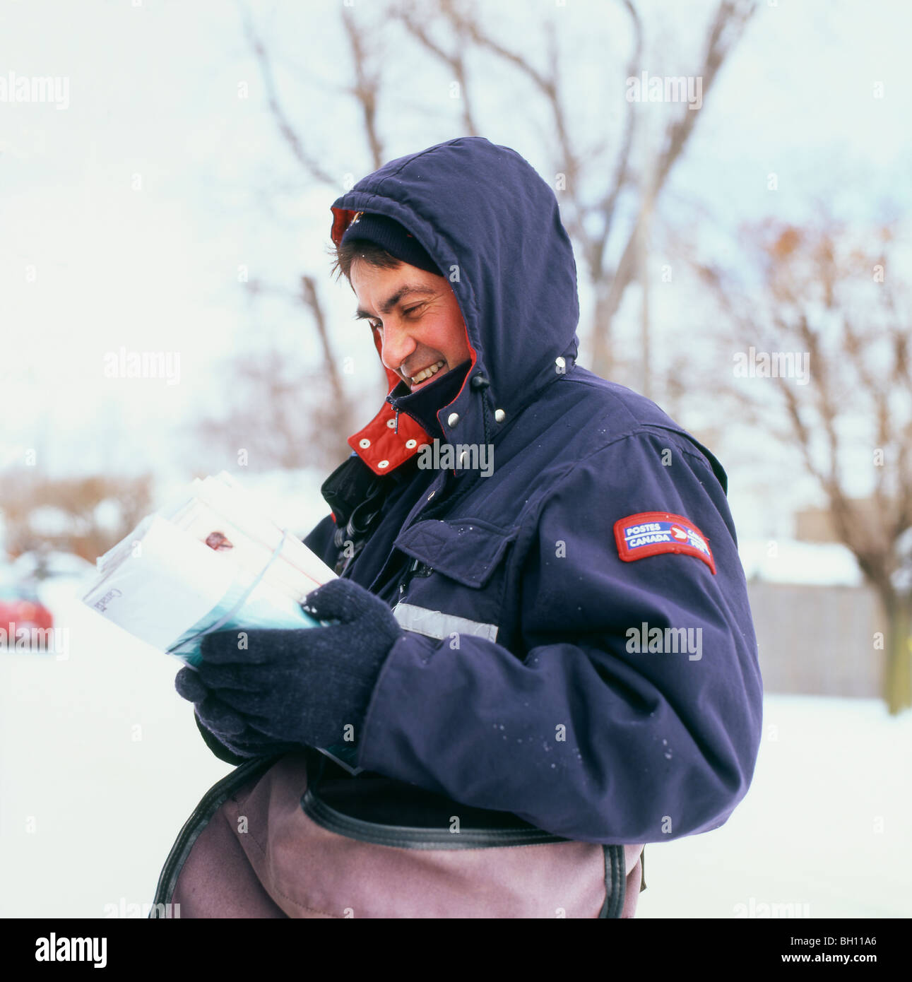 Mailman delivering  letters outside on a snowy day in winter Ontario Canada  KATHY DEWITT - Stock Image