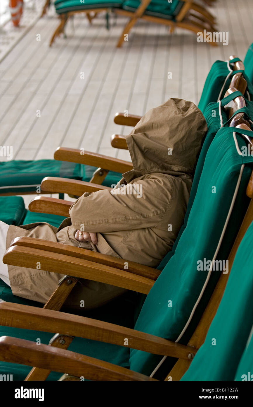 Woman wrapped against the chill on the QM2 - Stock Image
