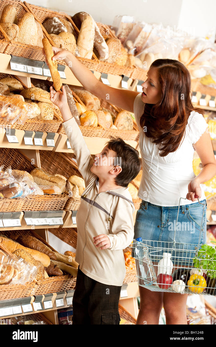 Grocery store shopping: Young woman with child buying bread in bakery department in supermarket - Stock Image