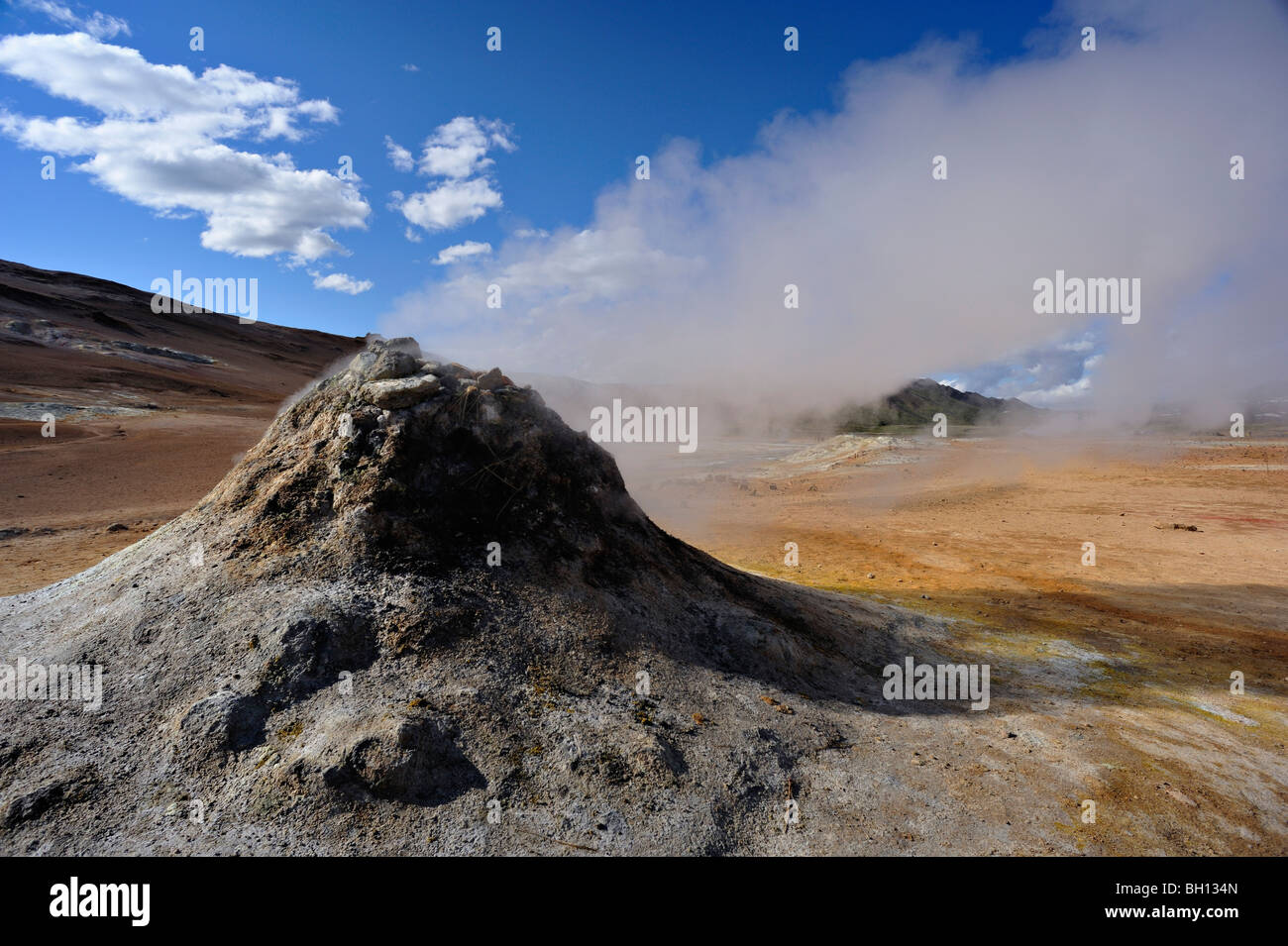 Steaming vent or fumarole under a beautiful summer sky in the geothermal area of Hverarond near Myvatn in northern - Stock Image