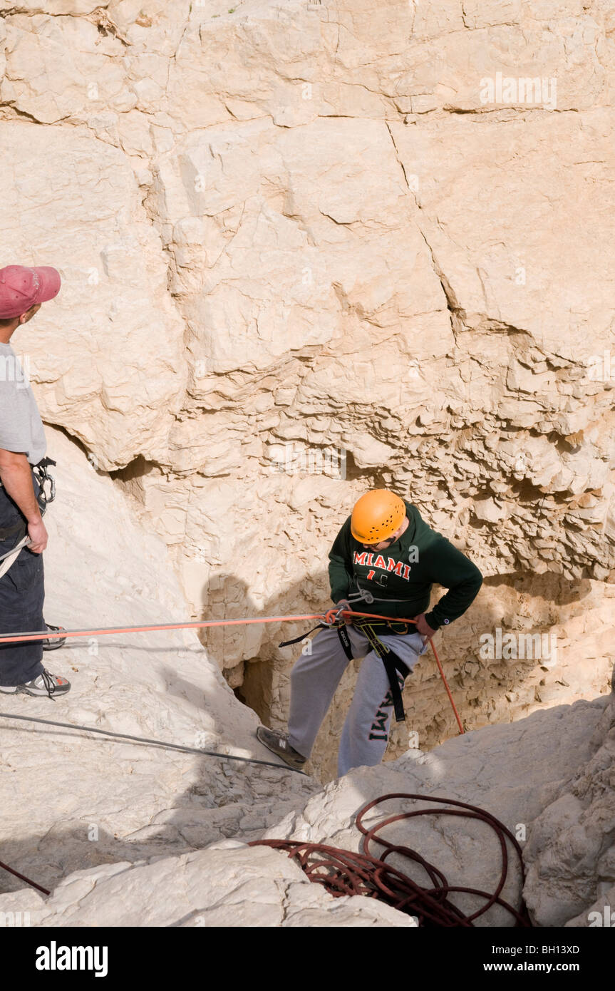 Israel, Dead Sea, Qumran, Group rappeling down a dry waterfall of the Qumran river - Stock Image