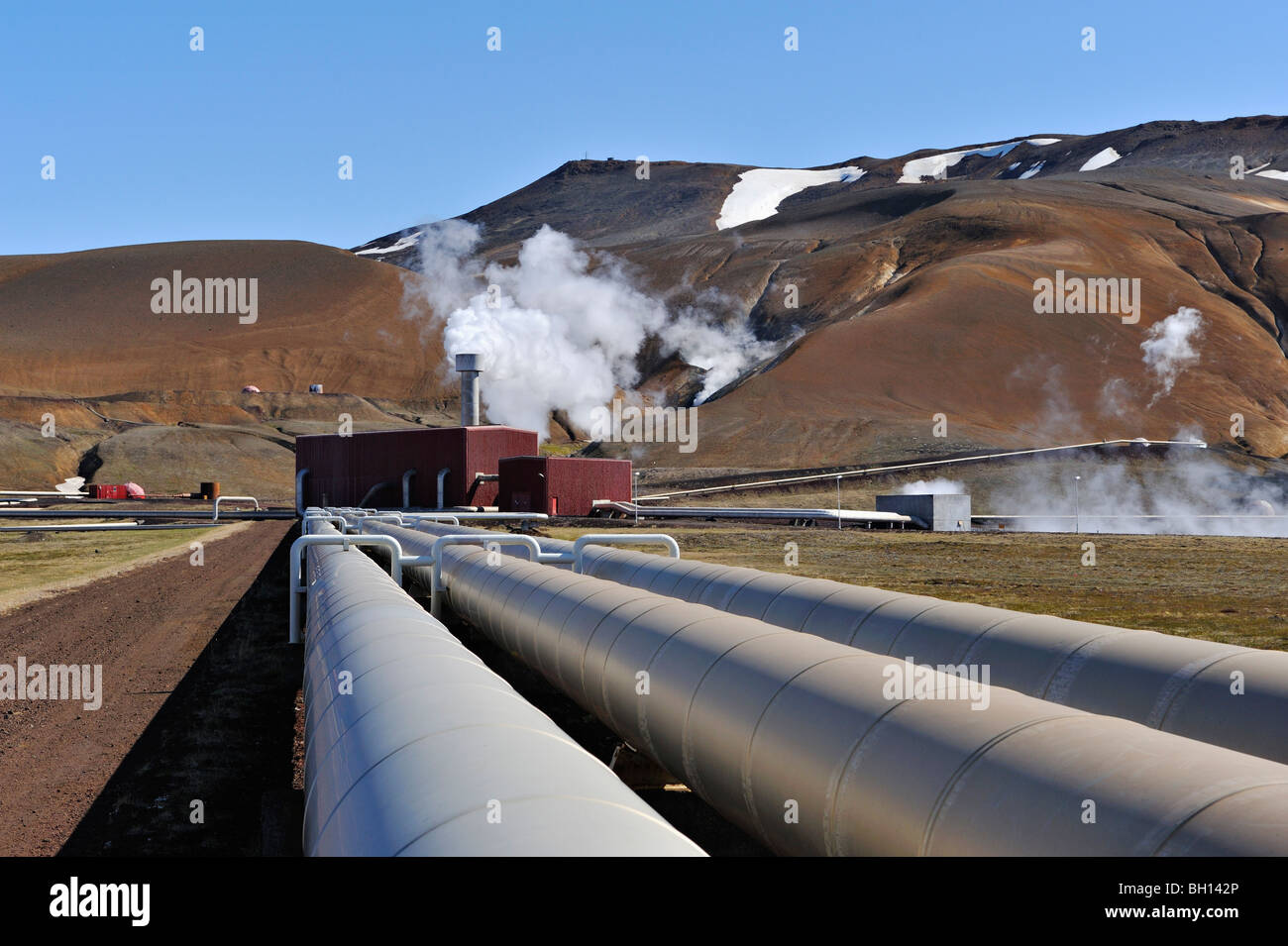 Pipework leads to exhaust steam gushing from equipment at the Krafla geothermal power plant near Myvatn, northern - Stock Image