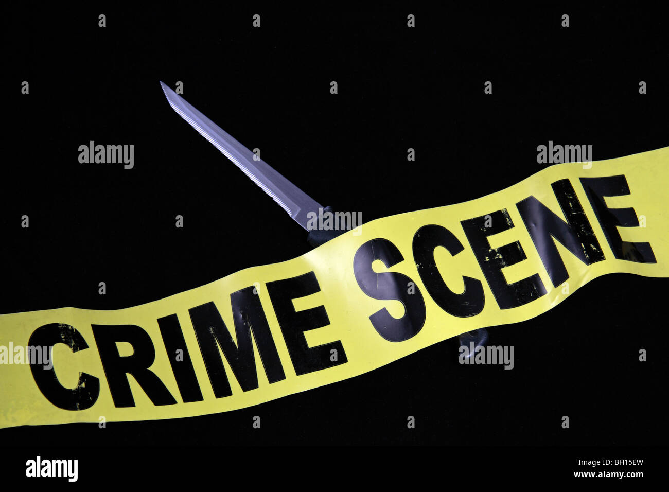 Crime Scene (Do Not Cross) tape lying on a serrated kitchen knife.  United Kingdom (UK). Jan 2010 - Stock Image
