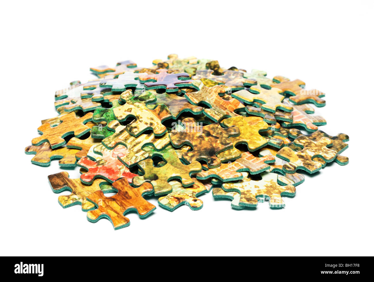 Pile of jigsaw pieces, cut out on white background - Stock Image