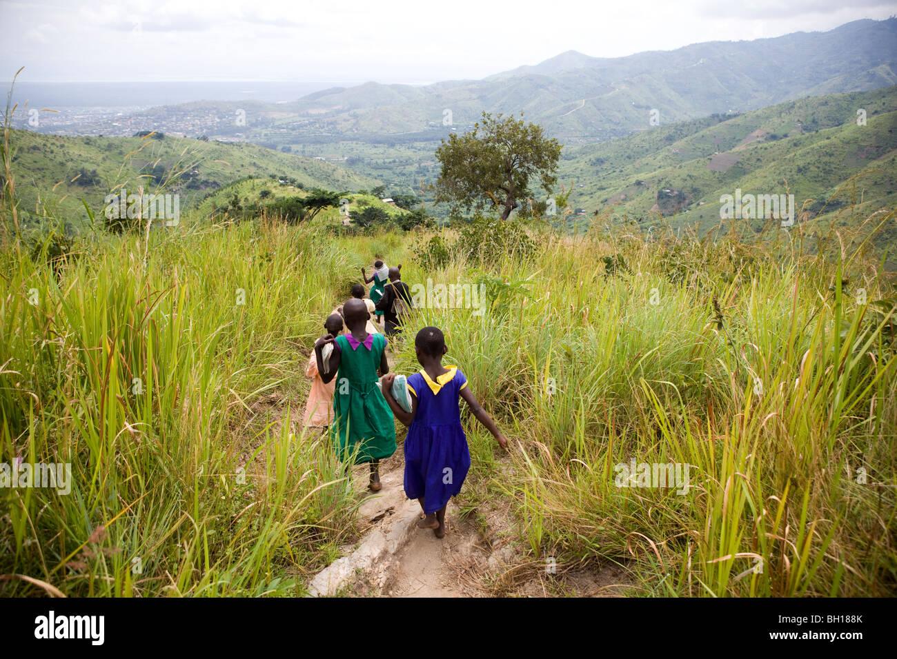 Children walking home after school in mountains in Uganda - Stock Image