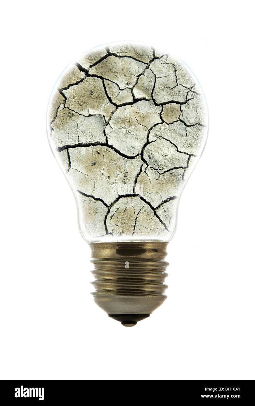 Cracked earth by drought inside incandescent lamp / bulb against white background - Stock Image