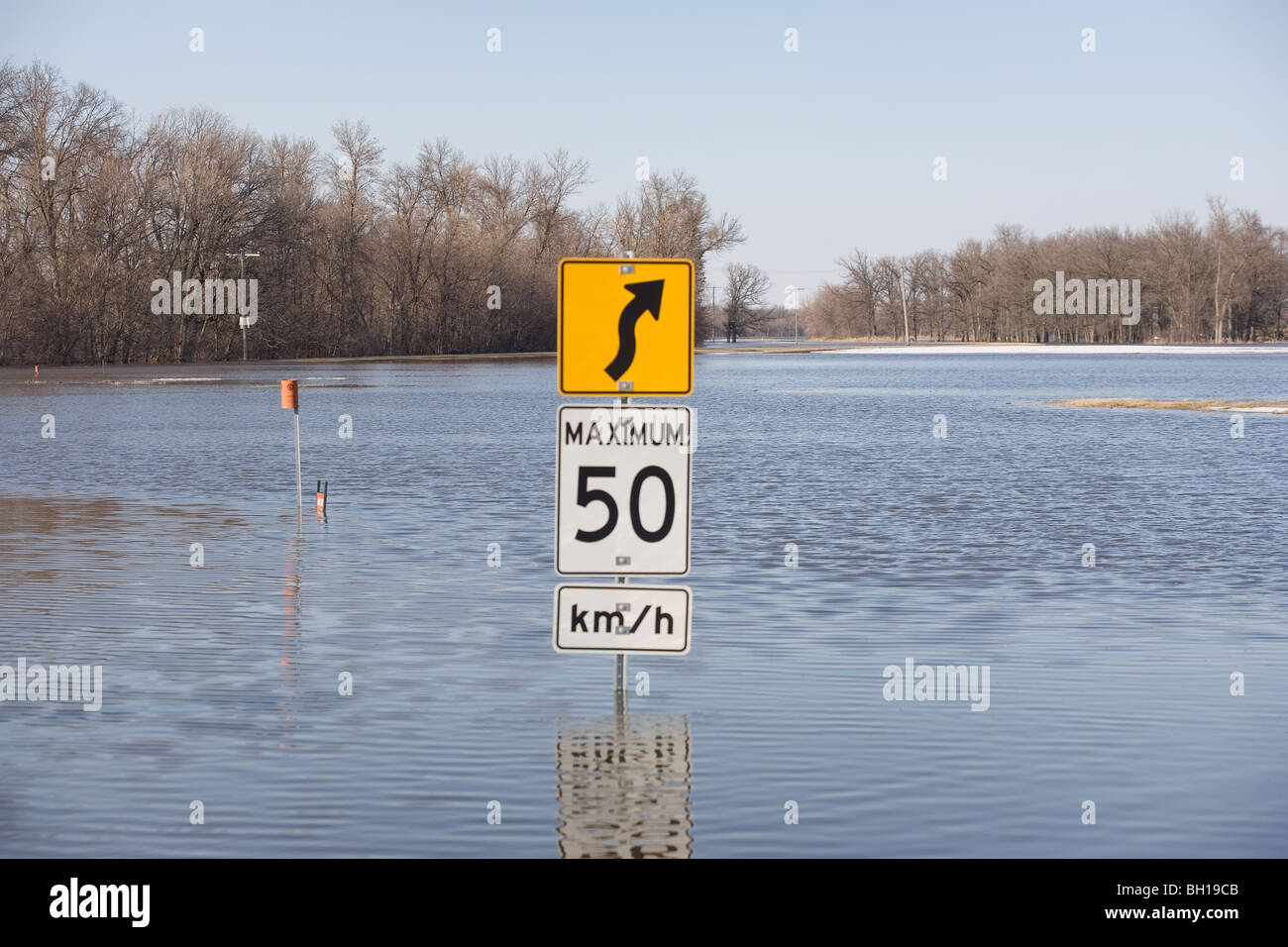 Road sign on road that is covered with floodwater from the Red River, Manitoba, Canada Stock Photo